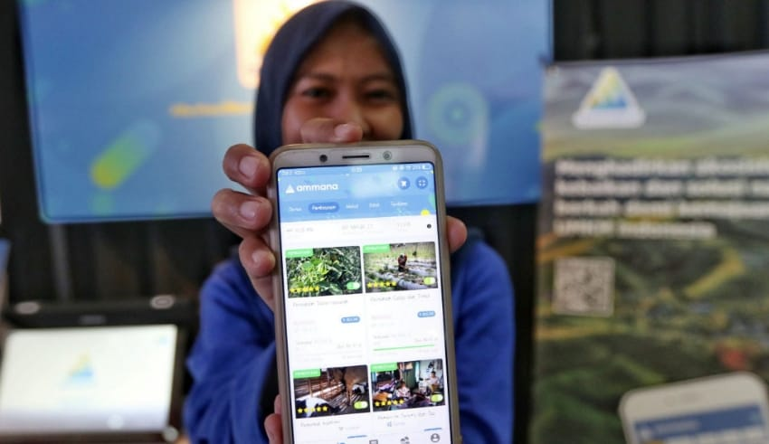 A woman shows fintech application Ammana on her smartphone