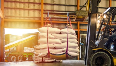 Forklift handling white sugar bags for stuffing into containers outside a warehouse