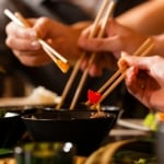 Young people eating in a Thai restaurant, they eating with chopsticks, close-up on hands and food