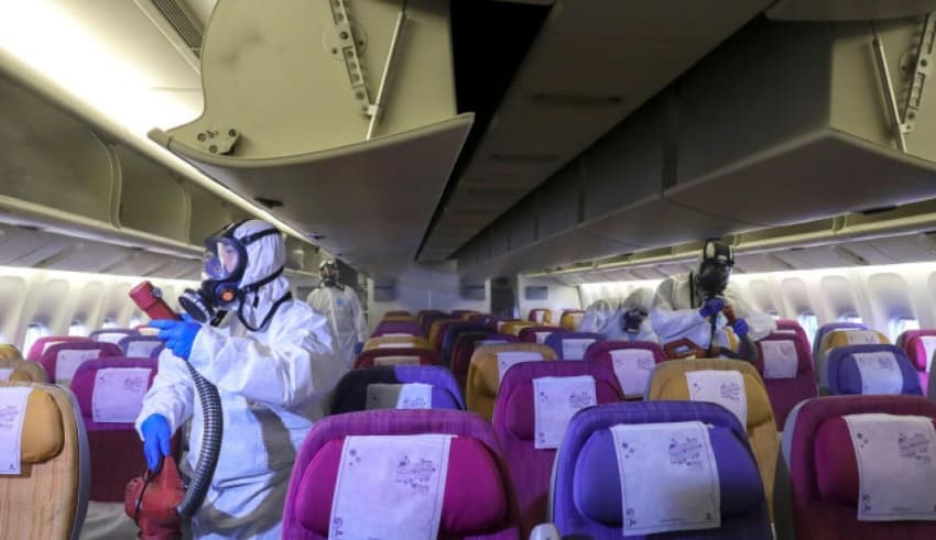 Members of a Thai Airways crew disinfect the cabin of an aircraft