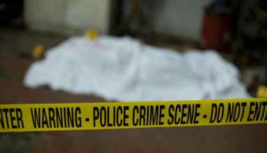 Crime scene band and covered dead body in background