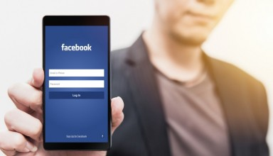 man show Facebook login page on his smartphone for using phone social app